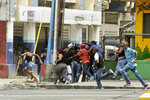 People run for cover as Panamanian police shoot rubber bullet into the air to disperse protesters from splinter groups who were throwing rocks at police and erecting burning barricades, in Colon, Panama, Tuesday, March 13, 2018. A march was called by a social and union movement to protest what they see as the slow pace of a multimillion-dollar plan to revitalize Colon's collapsed sewer system, water supply and housing (AP Photo/Arnulfo Franco)
