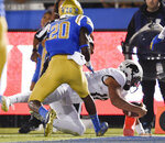 Colorado quarterback Steven Montez, back, scores a touchdown past UCLA defensive back Elisha Guidry during the first half of an NCAA college football game in Los Angeles, Saturday, Nov. 2, 2019. (AP Photo/Kelvin Kuo)