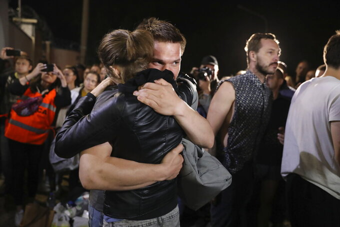 A couple hugs after being released from a detention center where protesters were detained during a mass rally following presidential election in Minsk, Belarus, Friday, Aug. 14, 2020. Nearly 7,000 people have been detained and hundreds injured in the clampdown on demonstrators protesting the official results that said Lukashenko won 80% of the vote and his top opposition challenger got only 10%. Police have broken up protests with stun grenades, tear gas, rubber bullets and severe beatings. (AP Photo)
