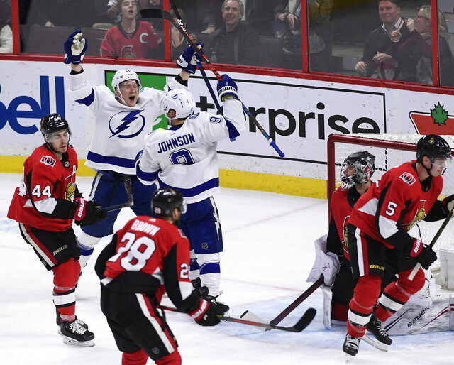 Tampa Bay Lightning center Tyler Johnson (9) celebrates his winning goal with left wing Ondrej Palat (18) as Ottawa Senators goaltender Craig Anderson (41) watches during third-period NHL hockey game action in Ottawa, Ontario, Saturday, Jan. 4, 2020. (Justin Tang/The Canadian Press via AP)