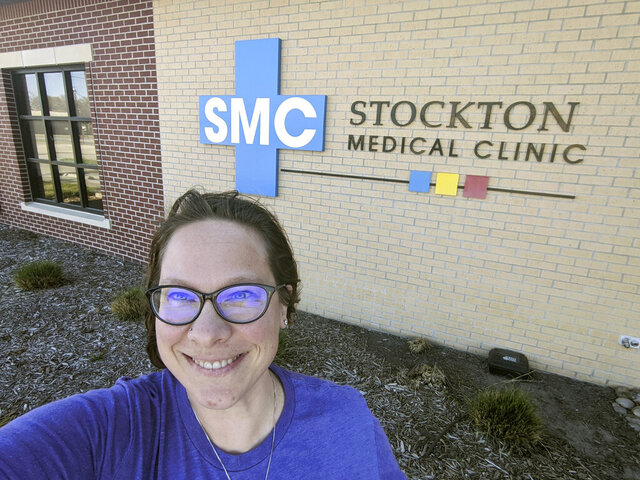 In this Wednesday, April 29, 2020 photo selfie provided by Dr. Beth Oller, Oller, a family physician, smiles while standing outside her medical clinic, just south of Main Street in Stockton, Kan. Oller began preaching social distancing well before her home of Rooks County confirmed its first coronavirus case and now she's nervous about the state reopening its economy too soon. (Dr. Beth Oller via AP)