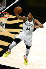 Milwaukee Bucks forward Giannis Antetokounmpo (34) goes in for a basket during the first half of the team's NBA basketball game against the Atlanta Hawks on Thursday, April 15, 2021, in Atlanta. (AP Photo/John Bazemore)