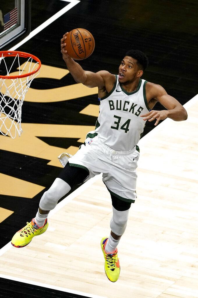 Milwaukee Bucks forward Giannis Antetokounmpo (34) goes in for a basket during the first half of the team's NBA basketball game against the Atlanta Hawks on Thursday, April 15, 2021, in Atlanta. (AP Photo/John Bazemore)