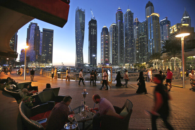 FILE - In this May 1, 2015, file photo, two men play backgammon while smoking a shisha water pipe at a restaurant overlooking the canal and the Dubai Marina neighborhood in Dubai, United Arab Emirates. Dubai again has loosened laws governing alcohol sales and possession as the sheikhdom tries to claw its way out of an economic depression worsened by the coronavirus pandemic. The virus worsened an already-gathering economic storm engulfing the emirate, which has seen mass layoffs thin the ranks of its foreign workforce and empty homes across its vast real-estate sector even amid slight signs of recovery. (AP Photo/Kamran Jebreili, File)