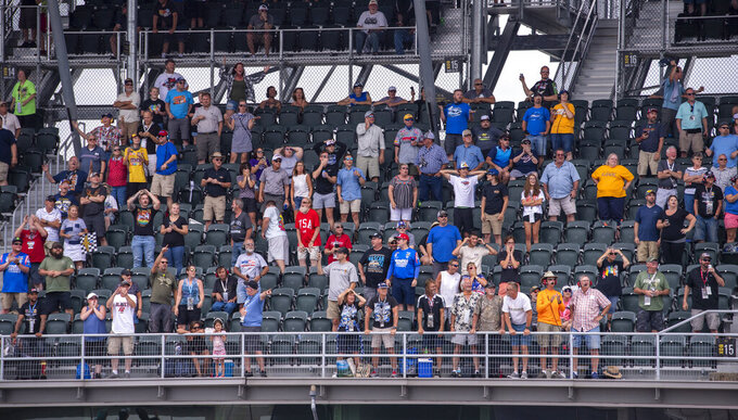 Fans react to a crash they watch on a monitor during a NASCAR Cup Series auto race at Indianapolis Motor Speedway, Sunday, Aug. 15, 2021, in Indianapolis. (AP Photo/Doug McSchooler)