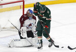 Minnesota Wild's Zach Parise, right, waits for the pass as Colorado Avalanche goalie Semyon Varlamov, of Russia, defends in the first period of an NHL hockey game, Tuesday, March 13, 2018, in St. Paul, Minn. (AP Photo/Jim Mone)