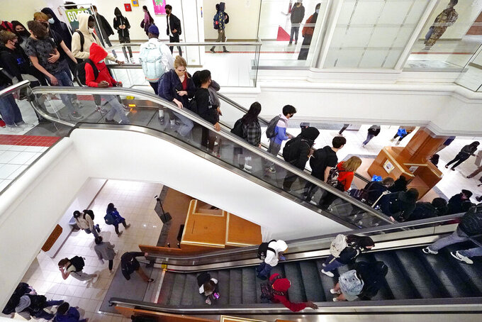 Students commute between classes at Downtown Burlington High School, Monday, March 22, 2021, in Burlington, Vt. Students who once shopped at a downtown mall are now attending high school in the mall's former Macy's department store, taking escalators to and from classes. The existing Burlington High School was closed last August after PCBs were found in the building. (AP Photo/Charles Krupa)