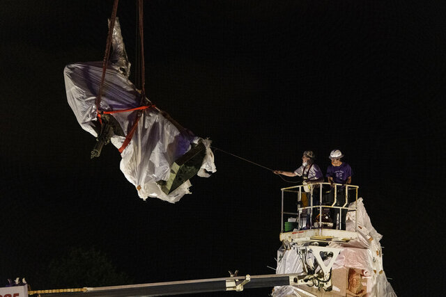 City municipal crews help guide the Christopher Columbus statue in Grant Park as it is removed by a crane, Friday, July 24, 2020, in Chicago. A statue of Christopher Columbus that drew chaotic protests in Chicago was taken down early Friday amid a plan by President Donald Trump to dispatch federal agents to the city. (Tyler LaRiviere/Sun-Times/Chicago Sun-Times via AP)
