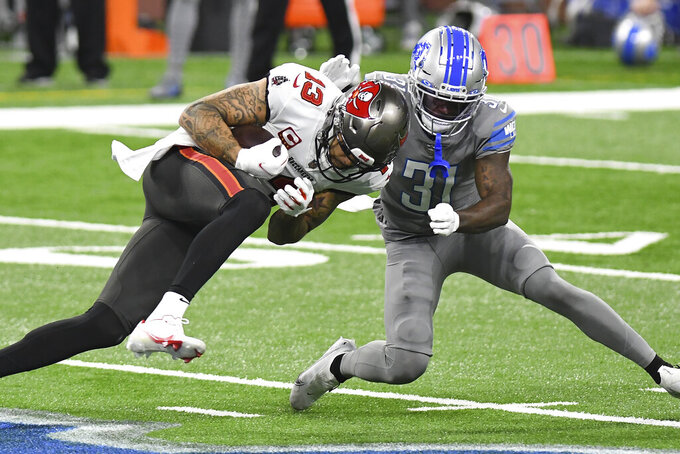 Tampa Bay Buccaneers wide receiver Mike Evans (13) runs into Detroit Lions corner back Tramaine Brock during the first half of an NFL football game, Saturday, Dec. 26, 2020, in Detroit. (AP Photo/Lon Horwedel)
