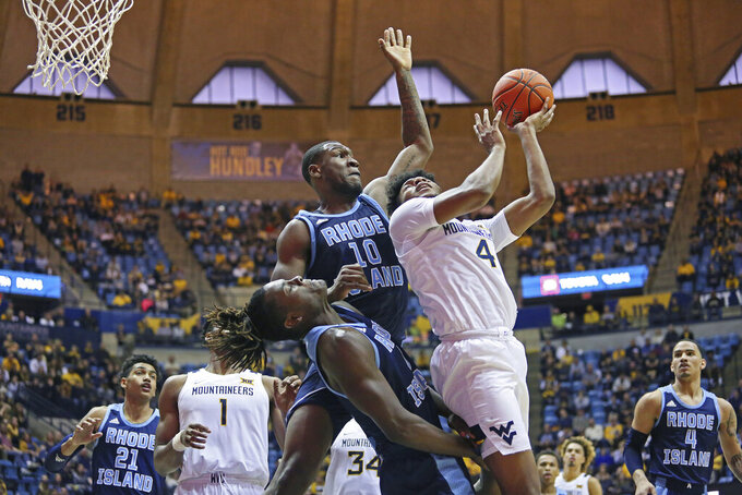 West Virginia guard Miles McBride (4) goes to shoot as he is defended by Rhode Island forwards Jermaine Harris (0) and Cyril Langevine (10) during the second half of an NCAA college basketball game Sunday, Dec. 1, 2019, in Morgantown, W.Va. (AP Photo/Kathleen Batten)