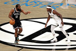 Brooklyn Nets guard James Harden, left, looks to pass around Milwaukee Bucks guard Jrue Holiday, right, during the first half of an NBA basketball game Monday, Jan. 18, 2021, in New York. (AP Photo/Adam Hunger)