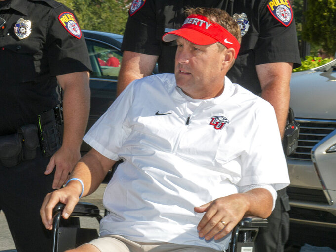FILE - In this Aug. 31, 2019, file photo, Liberty head football coach Hugh Freeze arrives to coach from a wheelchair in the coaches' box against Syracuse in an NCAA college football game in Lynchburg, Va. Freeze knows that part of his story as Liberty's football coach is about his own redemption, and he's fine with that. And in a season when school's administration is embroiled in very public legal battles, he hopes the No. 25 Flames offer some respite. (AP Photo/Matt Bell, File)