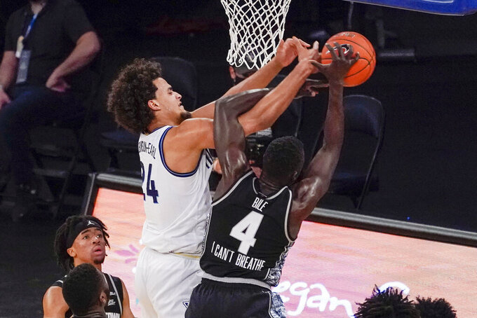 Villanova forward Jeremiah Robinson-Earl (24) and Georgetown forward Chudier Bile (4) vie for a rebound during the first half of an NCAA college basketball game in the quarterfinals of the Big East conference tournament, Thursday, March 11, 2021, in New York. (AP Photo/Mary Altaffer)