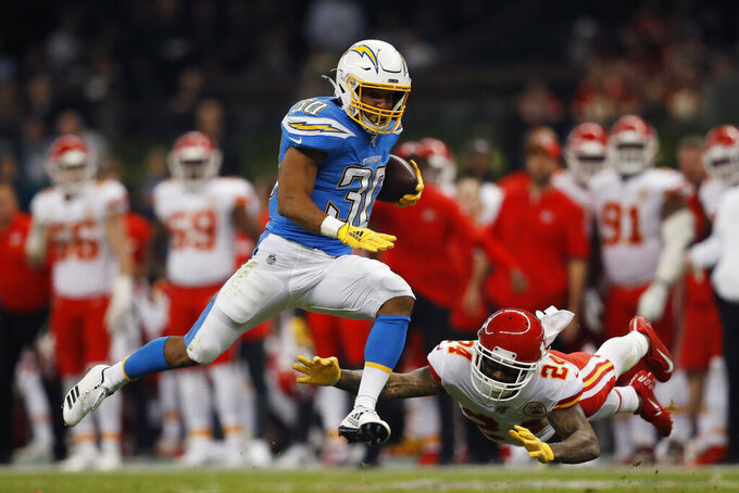 Los Angeles Chargers running back Austin Ekeler, left, gets past Kansas City Chiefs strong safety Jordan Lucas, right, during the first half of an NFL football game Monday, Nov. 18, 2019, in Mexico City. (AP Photo/Eduardo Verdugo)