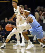 Colorado forward Lucas Siewert, middle, defends as San Diego guard Marion Humphrey moves the ball during the first half of an NCAA college basketball game Saturday, Nov. 16, 2019, in Boulder, Colo. (AP Photo/Cliff Grassmick)