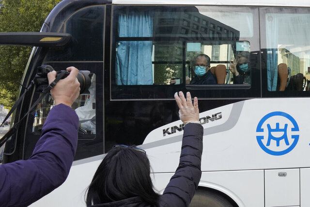 Workers wave off a team of experts from the World Health Organization who ended their quarantine and left the quarantine hotel in a bus in Wuhan in central China's Hubei province on Thursday, Jan. 28, 2021. The WHO team emerged from quarantine to start field work in a fact-finding mission on the origins of the virus that caused the COVID-19 pandemic. (AP Photo/Ng Han Guan)