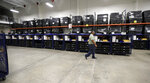 A worker passes voting equipment being staged for the upcoming primary elections at the Bear County Election offices, Tuesday, Feb. 13, 2018, in San Antonio. Texas will hold the first primary of 2018 on March 6. (AP Photo/Eric Gay)