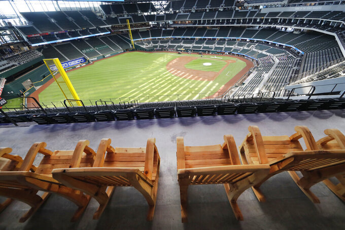 In this photo made Thursday, July 23, 2020, oversized rocking chairs sit ready for fans on the patio at the new Texas Rangers home baseball stadium named Globe Life Field in Arlington, Texas. The Texas Rangers' new stadium isn't retro and designers wanted the first next-generation ballpark. There is the full-panel retractable roof, the split seating levels offering full views of the ballpark with plenty of natural light. (AP Photo/LM Otero)