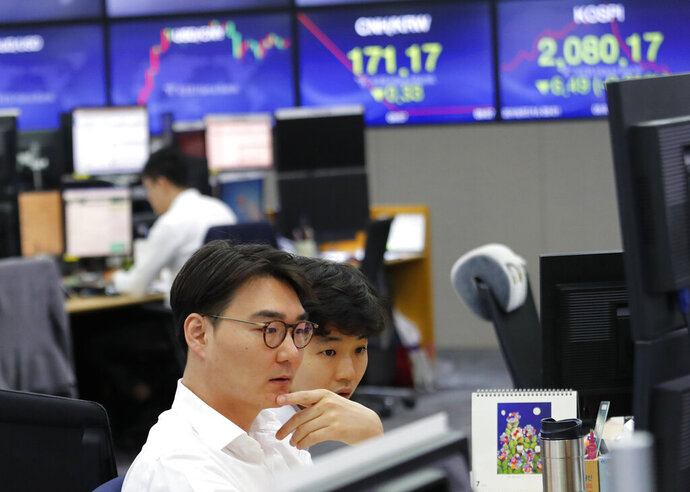 Currency traders watch monitors at the foreign exchange dealing room of the KEB Hana Bank headquarters in Seoul, South Korea, Monday, July 15, 2019. Shares are mixed in Asia, led by gains in Chinese markets after the government reported that the economy grew at the slowest pace in a decade in the last quarter. (AP Photo/Ahn Young-joon)