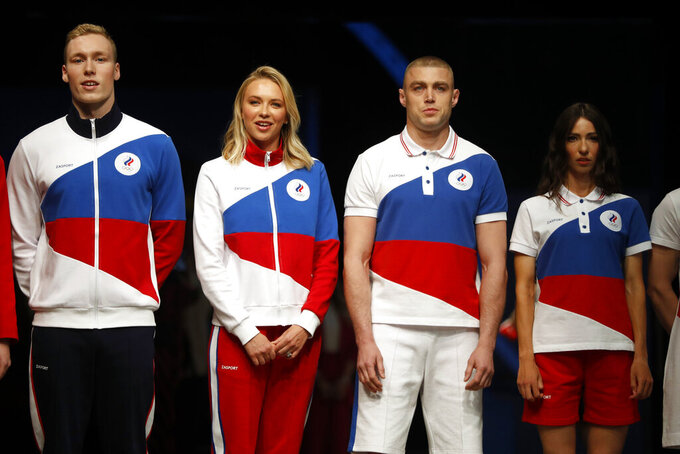 Athletes display the Olympic uniforms for Russian athletes in Moscow, Russia, Wednesday, April 14, 2021. Russia presents its Olympic kit for the Tokyo Games, which shouldn't depict any symbols of the country. Russian athletes will compete at the Tokyo Olympics as neutral after the Court of Arbitration for Sport last December banned Russia from using its name, flag and anthem at any world championships for the next two years because of state-backed doping. (AP Photo/Pavel Golovkin)