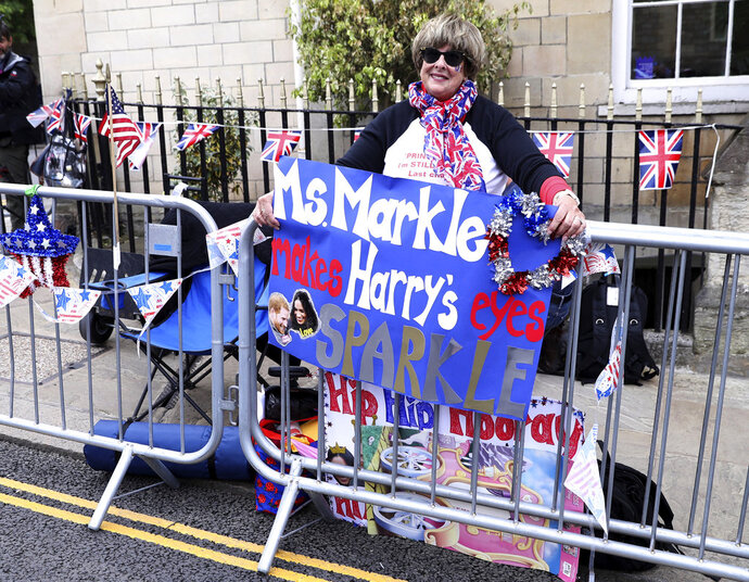 American royal fan Donna Werner, and who has come over to Britain specially for the upcoming royal wedding of Britain's Prince Harry and Meghan Markle, shows off her placards in her position along the carriage route in Windsor, England, Wednesday, May 16, 2018. Preparations continue in Windsor ahead of the royal wedding of Britain's Prince Harry and Meghan Markle Saturday May 19, which includes a 30 minute carriage route taking the couple round the town to wave to the crowds, some of whom are already taking up positions. (AP Photo/Alastair Grant)