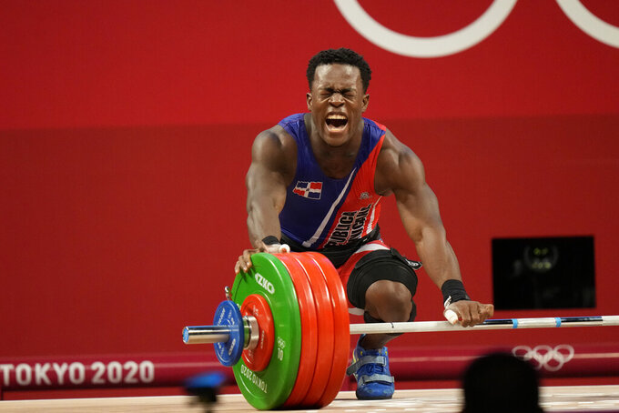 Zacarias Bonnat Michel of Dominican Republic reacts to an unsuccessful attempt as he competes in the men's 81kg weightlifting event, at the 2020 Summer Olympics, Saturday, July 31, 2021, in Tokyo, Japan. (AP Photo/Luca Bruno)