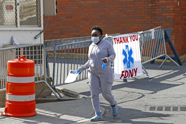 A woman leaves Elmhurst Hospital Center after being tested for COVID-19 or coronavirus during the current viral pandemic, Tuesday, April 7, 2020, in the Queens borough of New York. The new coronavirus causes mild or moderate symptoms for most people, but for some, especially older adults and people with existing health problems, it can cause more severe illness or death. (AP Photo/Kathy Willens)
