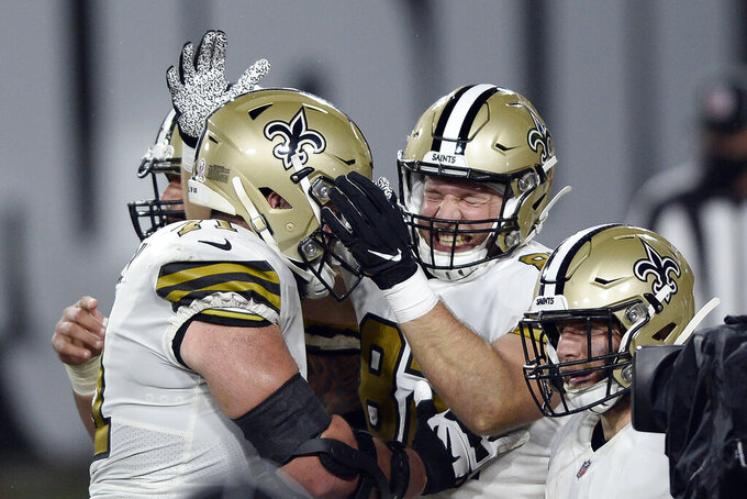 New Orleans Saints tight end Adam Trautman, center, celebrates with offensive tackle Ryan Ramczyk, left, after scoring against the Tampa Bay Buccaneers during the first half of an NFL football game Sunday, Nov. 8, 2020, in Tampa, Fla. (AP Photo/Jason Behnken)