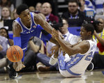 Duke's RJ Barrett, left, and North Carolina's Kenny Williams, right, chase a loose ball during the second half of an NCAA college basketball game in the Atlantic Coast Conference tournament in Charlotte, N.C., Friday, March 15, 2019. (AP Photo/Chuck Burton)