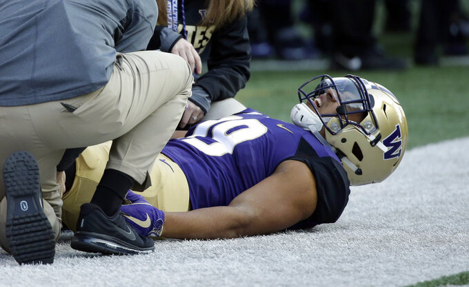FILE - In this Oct. 28, 2017, file photo, Washington's Hunter Bryant is treated after being injured against UCLA in the first half of an NCAA college football game in Seattle. After spending more than half the season recovering from knee surgery in June, Bryant has provided a boost for the 10th-ranked Huskies' offense heading into Friday's Pac-12 championship game against No. 17 Utah.  (AP Photo/Elaine Thompson, File)