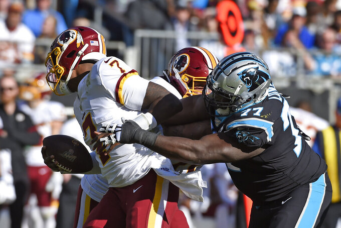Carolina Panthers defensive tackle Kyle Love (77) rushes Washington Redskins quarterback Dwayne Haskins (7) during the first half of an NFL football game in Charlotte, N.C., Sunday, Dec. 1, 2019. (AP Photo/Mike McCarn)