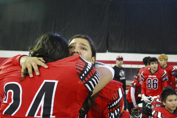 In this Nov. 8, 2019 photo, Jashawn Pease, right, embraces his brother Jayton, as they celebrate their 74-39 victory in the All Nations Football Conference championship in Vermillion, S.D.  Jashawn and Jayton Pease shed tears as the Crow Creek Chieftains won the first All Nations Conference championship, and then remembered their older brother _ one of too many American Indians to die by suicide on a reservation with the highest suicide rate in South Dakota. (AP Photo/Stephen Groves)