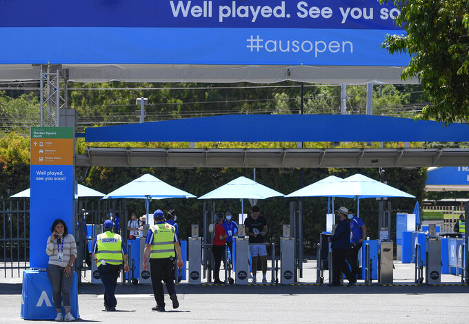 Officials man the entry gates to Melbourne Park in Melbourne, Australia, Wednesday, Feb. 3, 2021. The Australian Open site has the feel of a major this week with six tournaments being contested at Melbourne Park. Usually the tuneup tournaments Down Under are spread around the capital cities and some of the biggest stars have time off competitive play in the week before the first Grand Slam of the season. Not this year. The COVID-19 pandemic has changed the entire preparation for the Australian Open. (AP Photo/Andy Brownbill)
