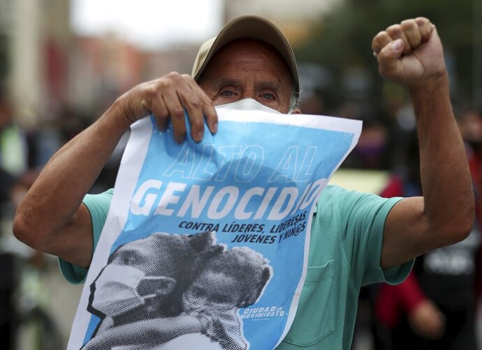 A protester holds a poster with a message that reads in Spanish: