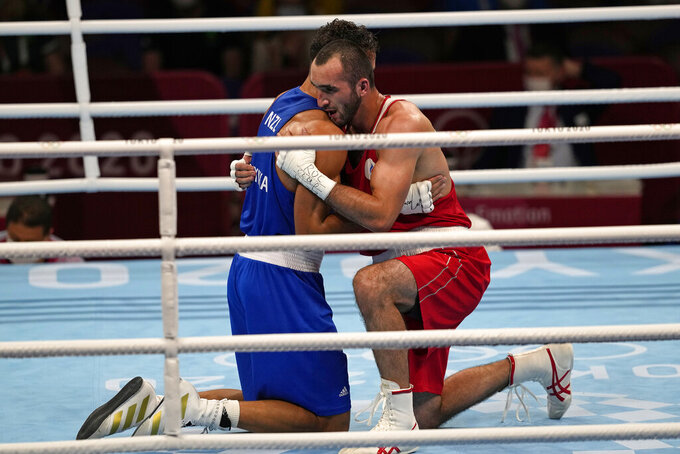 Russian Olympic Committee's Muslim Gadzhimagomedov, right, hugs New Zealand's David Nyika after winning their men's heavyweight 91kg semifinal boxing match at the 2020 Summer Olympics, Tuesday, Aug. 3, 2021, in Tokyo, Japan. (AP Photo/Themba Hadebe)