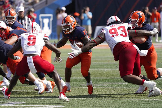 Illinois running back Reggie Love III caries the ball between Nebraska safety Marquel Dismuke (9) and defensive lineman Damion Daniels during the second half of an NCAA college football game Saturday, Aug. 28, 2021, in Champaign , Ill. Illinois won 30-22. (AP Photo/Charles Rex Arbogast)