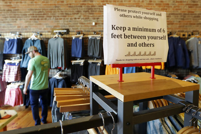 A sign reminding customers of social distancing is posted in the Bink's Outfitters store Wednesday, April 29, 2020, in Murfreesboro, Tenn. Retailers in 89 of Tennessee's 95 counties were allowed to reopen Wednesday with restrictions as the state begins the next wave of reopening its economy during the coronavirus pandemic. (AP Photo/Mark Humphrey)