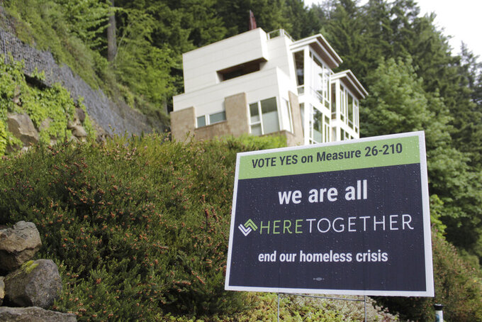 """FILE - In this May 14, 2020, file photo, a campaign sign urging people to vote """"Yes"""" on Measure 26-210, which would approve taxes on personal income and business profits to raise $2.5 billion over a decade to fight homelessness, is displayed near an upscale home in Portland, Ore. A measure to tax the incomes of the wealthiest residents and the profits of the biggest businesses to raise $2.5 billion over a decade to address the homeless crisis sailed to victory in the Portland, Oregon metropolitan region even as the state faces crippling revenue losses and record-high unemployment. Nearly 60% of voters in the three counties that make up the greater Portland region approved the tax amid a greatest economic turmoil in years, a sign of just how intractable the homeless problem has become in the liberal Pacific Northwest city. (AP Photo/Gillian Flaccus, File)"""