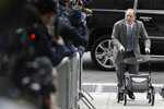 Harvey Weinstein talks to reporters as he arrives at a Manhattan courthouse for his rape trial in New York, Tuesday, Feb. 18, 2020. (AP Photo/Seth Wenig)