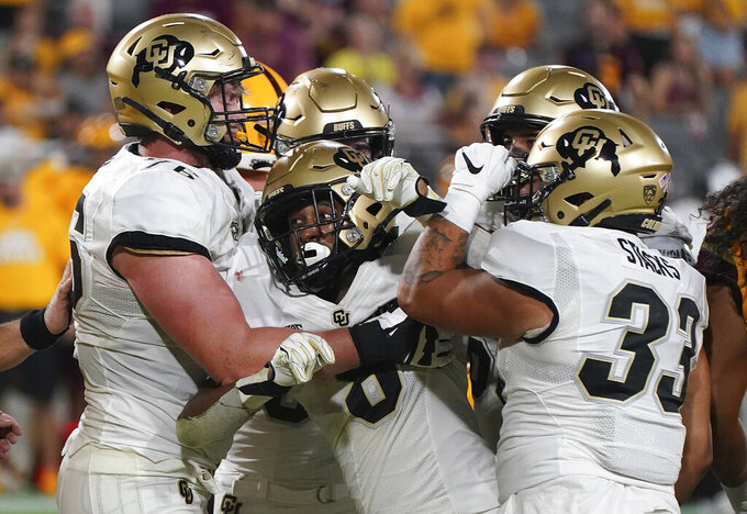 Colorado tailback Alex Fontenot (8) is mobbed by teammates after scoring a touchdown against Arizona State during the second half of an NCAA college football game Saturday, Sept. 25, 2021, in Tempe, Ariz. (AP Photo/Darryl Webb)