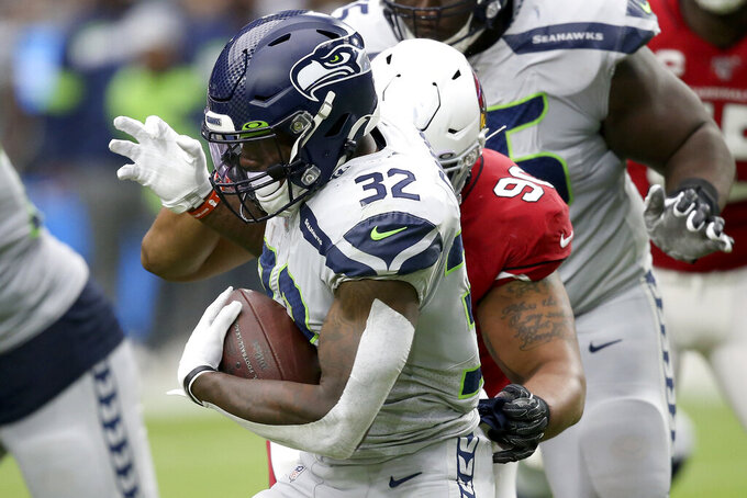 Seattle Seahawks running back Chris Carson (32) runs as Arizona Cardinals defensive end Jonathan Bullard defends during the first half of an NFL football game, Sunday, Sept. 29, 2019, in Glendale, Ariz. (AP Photo/Ross D. Franklin)