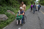 Honduran migrant Omar Orella pushes fellow migrant Nery Maldonado Tejeda in a wheelchair, as they travel with hundreds of other Honduran migrants making their way the U.S., near Chiquimula, Guatemala, Tuesday, Oct. 16, 2018. Maldonado said he lost his legs in 2015 while riding