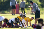 Washington quarterbacks Dwayne Haskins Jr., third from left, Alex Smith, and Kyle Allen, rear, talk with head coach Ron Rivera right, during practice at the team's NFL football training facility, Tuesday, Aug. 18, 2020, in Ashburn, Va. (AP Photo/Alex Brandon)