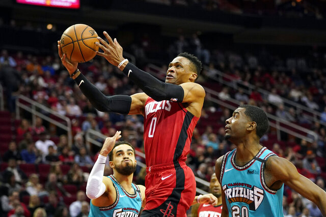 Houston Rockets' Russell Westbrook (0) goes up for a shot as Memphis Grizzlies' Josh Jackson (20) and Tyus Jones, left, defend during the first half of an NBA basketball game Wednesday, Feb. 26, 2020, in Houston. (AP Photo/David J. Phillip)
