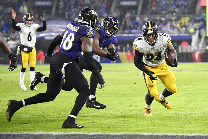 Pittsburgh Steelers running back Benny Snell, right, runs toward the end zone while scoring a touchdown as Baltimore Ravens inside linebacker Patrick Onwuasor (48) and linebacker Jaylon Ferguson try to stop him during the first half of an NFL football game, Sunday, Dec. 29, 2019, in Baltimore. Steelers quarterback Devlin Hodges (6) reacts on the play. (AP Photo/Nick Wass)