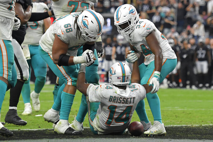 Miami Dolphins offensive guard Robert Hunt (68) and running back Malcolm Brown (34) help up quarterback Jacoby Brissett (14) after Brissett scored a touchdown against the Las Vegas Raiders during the second half of an NFL football game, Sunday, Sept. 26, 2021, in Las Vegas. (AP Photo/David Becker)