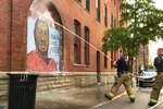 Lafayette firefighters use a hose to remove white paint that was thrown at the George Floyd mural painted in the summer of 2020 at 6th and Ferry Streets, Monday, Aug. 30, 2021, in Lafayette, Ind. A mural of George Floyd has been defaced for the fourth time since it was painted in a northwest Indiana city last year to honor Floyd following his death in Minneapolis police custody.  (Nikos Frazier/Journal & Courier via AP)