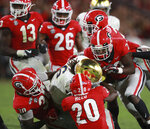 September 21, 2019 Athens: The Georgia defenders Tae Crowder (from left), J.R. Reed, and Mark Webb gang tackle Notre Dame running back Tony Jones Jr. during the third quarter of an NCAA college football game Saturday, Sept. 21, 2019, in Athens, Ga. (Curtis Compton/Atlanta Journal Constitution via AP)