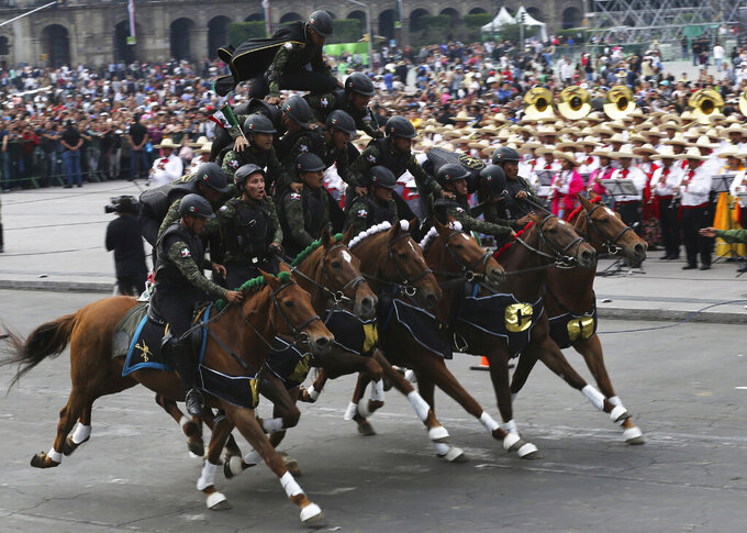 In this Wednesday, Nov. 20, 2019 photo, soldiers form a pyramid atop a team of horses during a parade marking the 109th anniversary of the Mexican Revolution, at the Zocalo in Mexico City. More than a 1,000 participants dressed in time period clothing and acted out historical scenes. (AP Photo/Marco Ugarte)