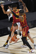 BYU's Kolby Lee, center, struggles between the defense of Southern California's Max Agbonkpolo, left, and Southern California's Chevez Goodwin, right, in the first half of an NCAA college basketball game, Tuesday, Dec. 1, 2020, in Uncasville, Conn. (AP Photo/Jessica Hill)
